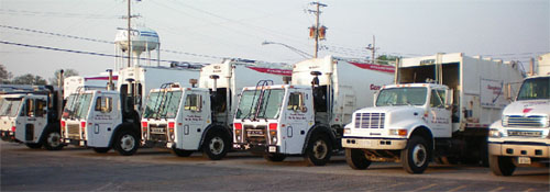 6 garbage trucks parked side-by-side in a lot